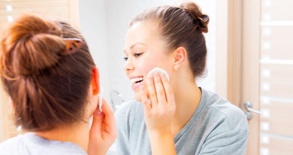 Beauty teenage girl cleaning her face with cotton pad at home